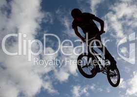 Slhouetted biker boy doing stunts