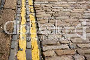 Modern (no parking) double yellow lines along ancient cobble stones