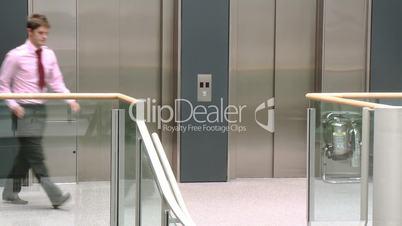 Geschäftsmann telefoniert vor dem Fahrstuhl