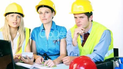 Arbeitsteam sitzt mit Schutzhelmen im Büro
