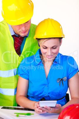 Mann und Frau mit Schutzhelm im Büro