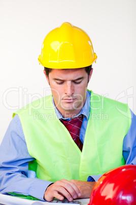 Junger Mann mit Schutzhelm am Schreibtisch.