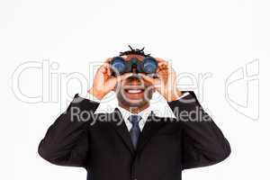 Handsome businessman holding binoculars upwards