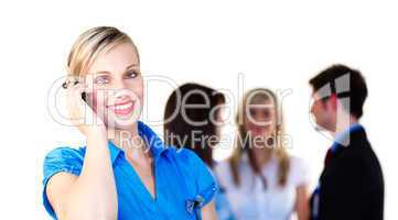 Businesswoman on phone with her team in the background