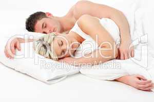 Blonde girl sleeping with a boy in bed