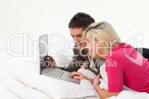 Girl using a latop in bed with her boyfriend