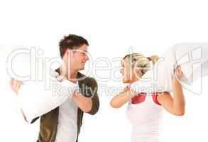 Young girl and boy having a pillow fight