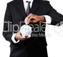 Close-up of a Businessman putting money in his piggy bank
