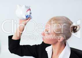 Sad Business woman looking into Piggy Bank
