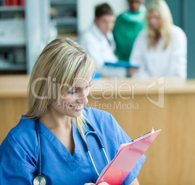 Blonde Ärztin - im Hintergrund Klinikpersonal