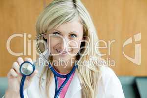 Lächelnde blonde Ärztin hält ihr Stethoskop