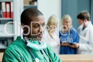 Arzt im grünen OP-Kittel mit Stethoskop