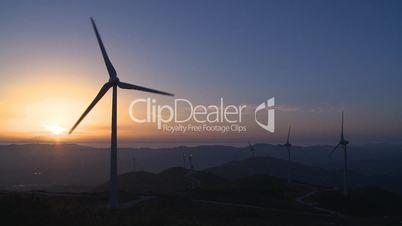 Wind turbine generator in the mount at sunset