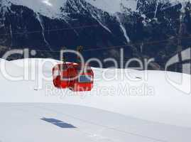 Red cabines of cable-way against black and white mountainside
