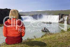 Woman Sitting At Godafoss Waterfall