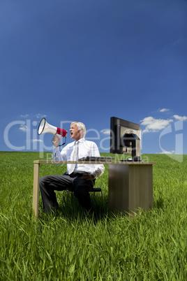 Man Using Megaphone In A Green Field