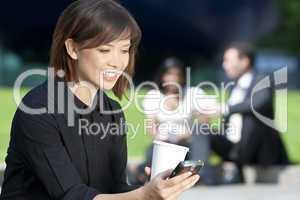 Beautiful Young Asian Woman Texting and Drinking Coffee