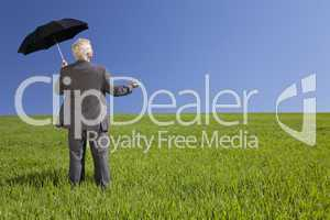Businessman In A Green Field With An Umbrella