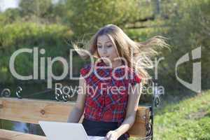 Girl on bench with laptop  in autumn park- wind blow up hair