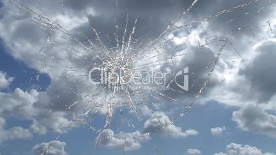Broken window, cracked glass against sky time lapse