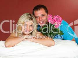 Couple on sofa holding a rose bouquet