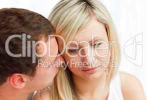Junger Mann raunt einer Frau etwas ins Ohr