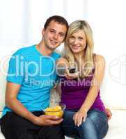 Happy couple watching television and eating crisps