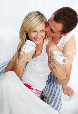 Junges Paar trinkt Kaffee im Bett