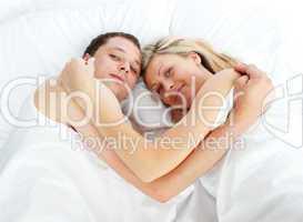 Junges Paar liegt Arm in Arm im Bett