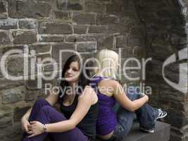 Girls sitting in front of a wall