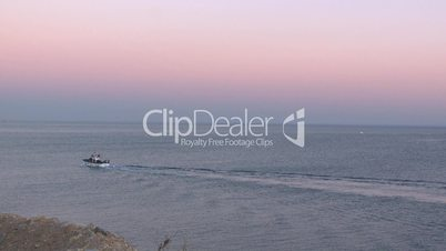 Fishing boat coming to port at sunset