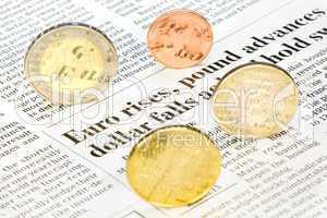 Euromünzen rollen über Zeitungsseite