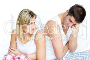 Angry couple having an argument in bed