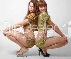 Two girls squatting down, side view