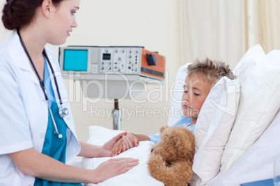 Female doctor examining a child in bed