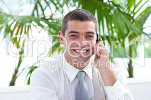 Friendly businessman on phone sitting on a couch