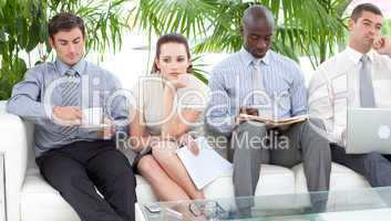Bored business people sitting on a sofa waiting for an interview