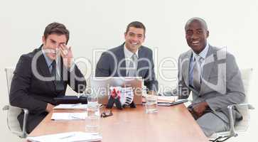 Businessmen in a meeting smiling at the camera