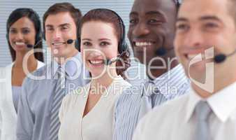 Smiling businesswoman working in a call center in a line