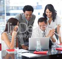Multi-ethnic business team working together with a laptop