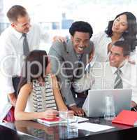 Smiling multi-ethnic business team working with a laptop