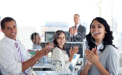 Businessteam applauding a colleague after a presentation