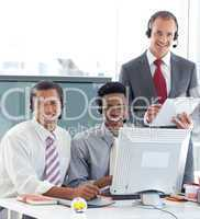Manager talking to two businessmen in call center