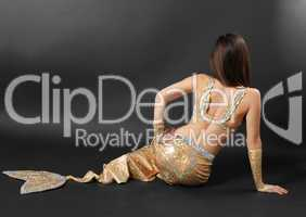 Sitting girl in shining suit with fish tail