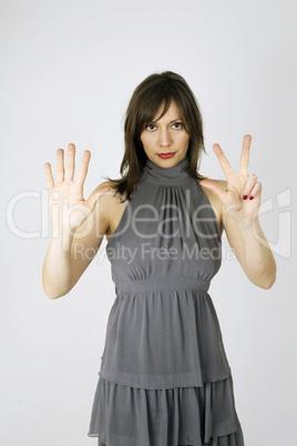 Eine junge Frau zeigt die Zahl acht an