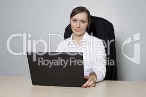 Junge Geschäftsfrau sitzt vor ihrem Computer