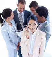 Geschäftsfrau telefoniert und ihr Team steht dahinter