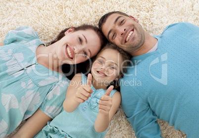 Parents and daughter on floor with thumbs up