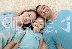 Smiling parents and girl on floor with heads together