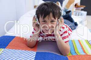 Smiling boy listening to music in bed with headphones on